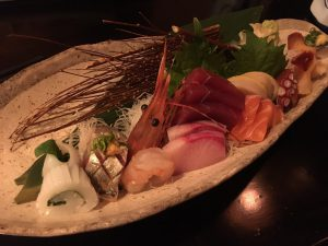 A beautifully styled platter of sashimi, featuring a large shrimp head
