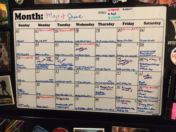 """A whiteboard calendar starting May 10 and ending June 20 with entries color-coded for exercise, food, paycheck, and """"special""""."""